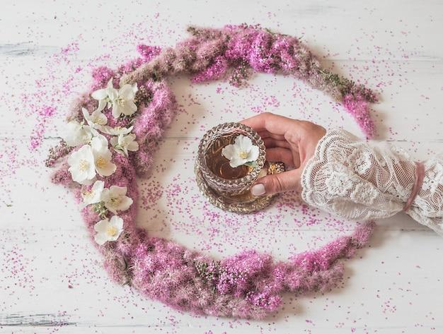 Composição de flores. mão da garota segura um copo de chá em uma composição de flores rosa em branco