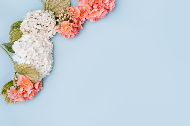 Composição de flores mistas sobre fundo azul. vista de cima, copie o espaço.