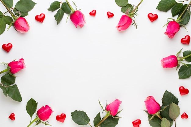 Composição de flores. moldura feita de rosa vermelha em branco.