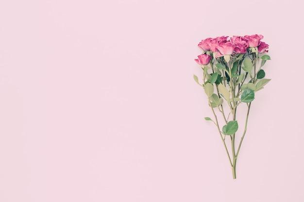 Composição de flores. moldura feita de rosa vermelha em madeira branca.