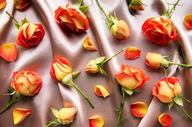 Composição de flores. moldura feita de rosas vermelhas e folhas em fundo de seda. vista superior, configuração plana, espaço de cópia