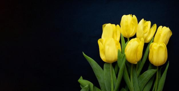 Composição de flores. moldura feita de tulipas amarelas sobre fundo azul. dia dos namorados, dia das mães e conceito de dia das mulheres. camada plana, vista superior.