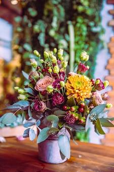 Composição de flores no balde rosas crisântemo vista lateral