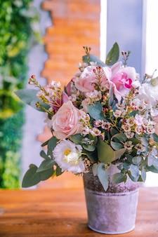 Composição de flores no balde rosas orquídea lithianthus vista lateral
