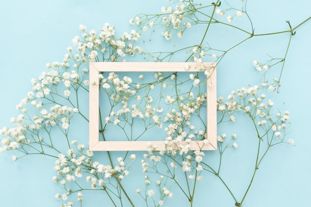 Composição de flores romântica. flores brancas do gypsophila, quadro da foto no fundo azul pastel.