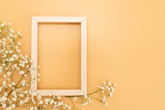 Composição de flores romântica. flores brancas do gypsophila, quadro da foto no fundo do rosa pastel.