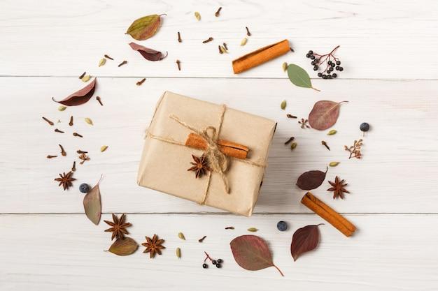 Composição de flores secas de outono, folhas, frutos, paus de canela, cravo e abrunheiro presente em papel artesanal.