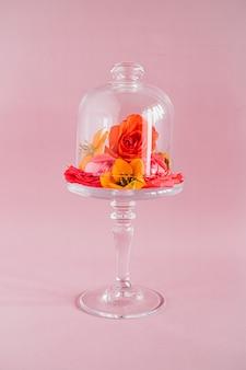 Composição de flores tropicais coloridas no bolo de vidro fique em rosa, composição de tendências