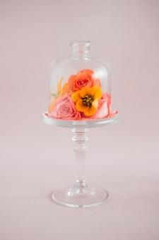 Composição de flores tropicais coloridas no carrinho do bolo de vidro, composição de tendências