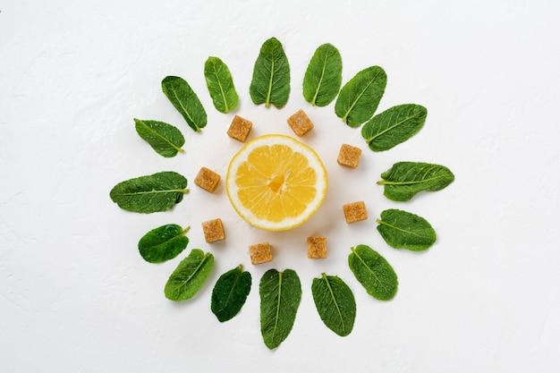 Composição de folhas de hortelã, limão e pedaços de açúcar de cana em um fundo branco de concreto velho.