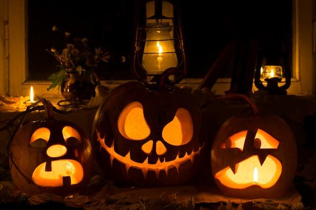 Composição de fotos de três abóboras no halloween. chorando, jack e abóboras assustadas contra uma janela velha, folhas secas