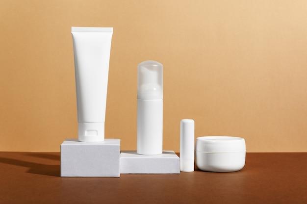 Composição de frascos de cosméticos de cuidados faciais e corporais em fundo marrom.