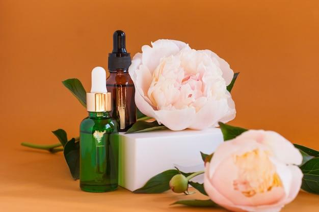 Composição de frascos de vidro escuro com produtos cosméticos e médicos. frascos com adereços ou soro de remédio para alergia, óleos com peônia branca sobre fundo bege.