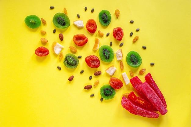 Composição de frutas cristalizadas multicoloridas em um fundo amarelo. vista de cima. um lugar para texto. foto de alta qualidade