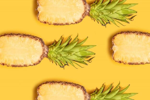 Composição de frutas de verão. abacaxis frescos metade cortada em fundo amarelo