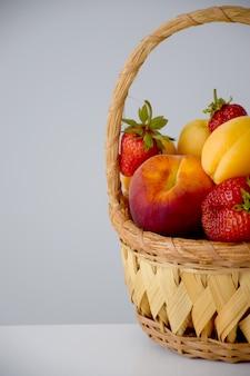 Composição de frutas e bagas frescas na cesta de vime cortada na metade