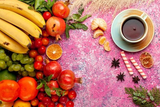 Composição de frutas frescas de vista frontal com uma xícara de chá na mesa rosa claro