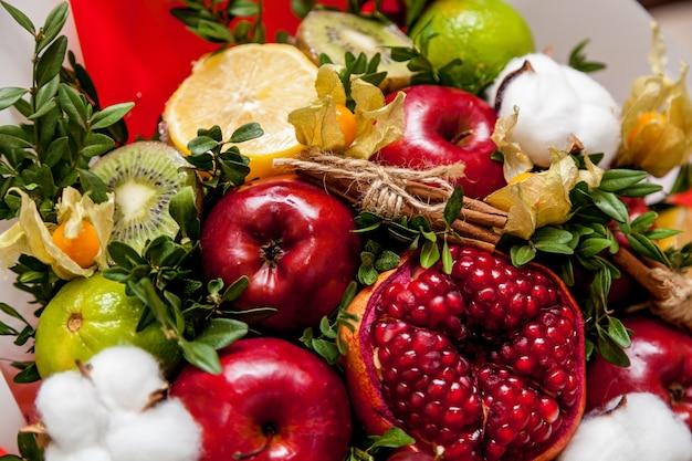 Composição de frutas frescas e brilhantes. buquê de frutas de romã, uvas, maçãs, kiwi, laranja, limão, marrom e algodão