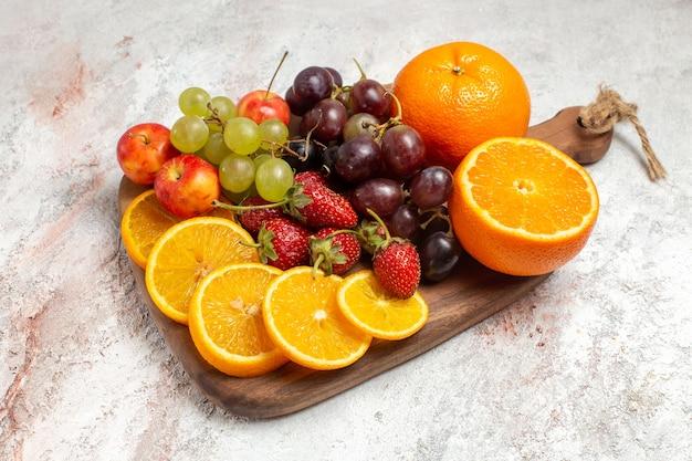 Composição de frutas frescas, laranja, uvas e morangos no espaço em branco de vista frontal