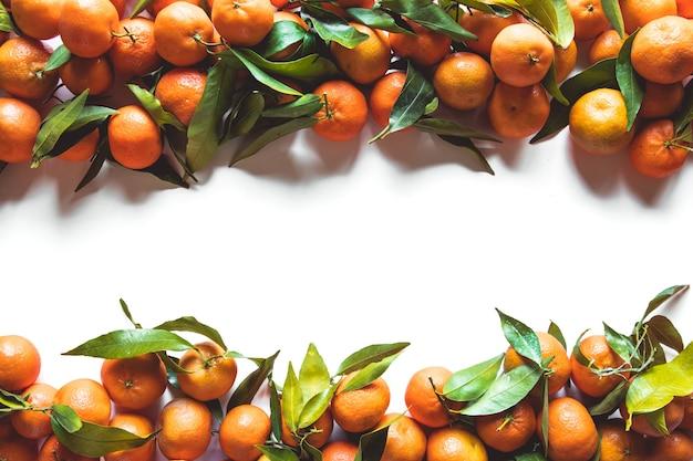 Composição de frutas laranjas com folhas verdes e fatia em fundo branco de madeira, vista superior