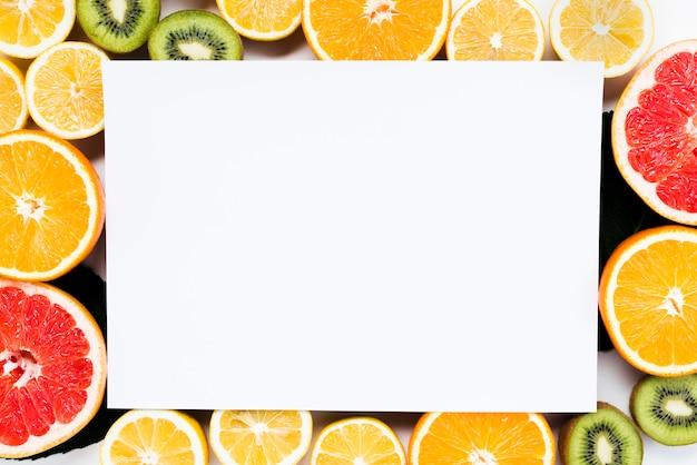 Composição de frutas tropicais coloridas cortadas com pedaço de papel branco