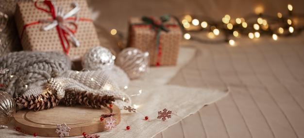 Composição de fundo de natal de pinhas, guirlandas, caixas de presente, detalhes de decoração para casa e espaço de cópia de luzes desfocadas.
