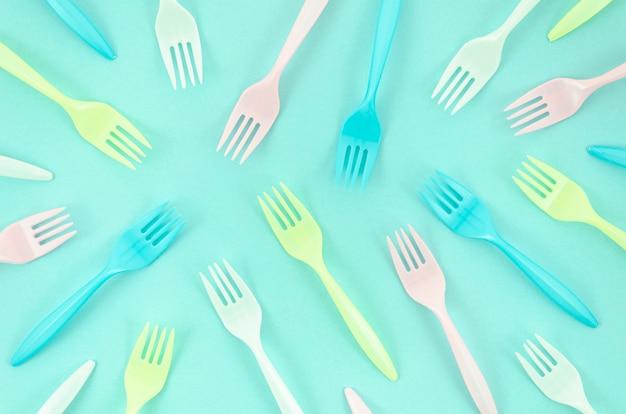 Composição de garfos coloridos sobre fundo turquesa