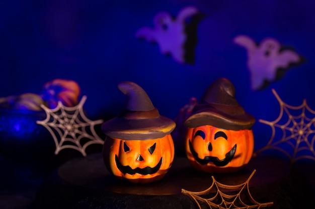 Composição de halloween com abóboras, teias de aranha e fantasmas no quarto escuro temperamental. cartão de saudação decorado assustador criativo. conceito de férias de estilo de vida.