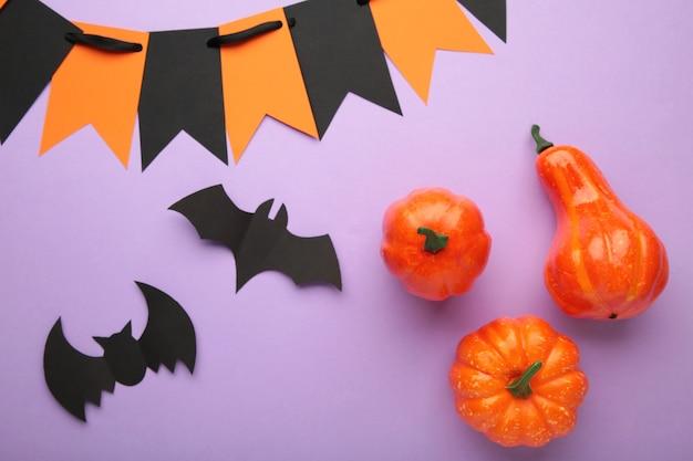 Composição de halloween com morcegos e abóboras em fundo roxo. vista de cima. vista do topo