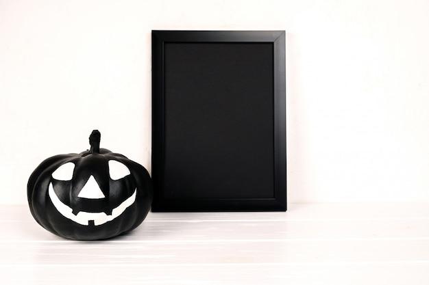 Composição de halloween. moldura preta e arte em papel abandonada aldeia, abóbora em branco.