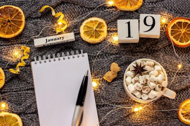 Composição de inverno. calendário de madeira 19 de janeiro xícara de cacau com marshmallow, bloco de notas aberto vazio com caneta, laranjas secas, guirlanda de luz em fundo cinza de malha. mockup plano de vista superior
