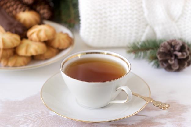 Composição de inverno com chá e biscoitos com cones e ramos de abeto.