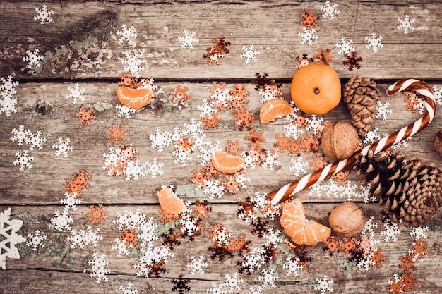 Composição de inverno com pirulito, pinhas, nozes e tangerina