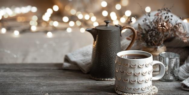 Composição de inverno com uma bela xícara de bebida quente e um bule em um fundo desfocado com bokeh.