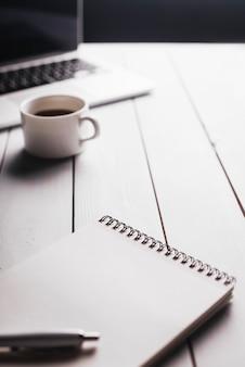 Composição de laptop e bloco de notas na mesa