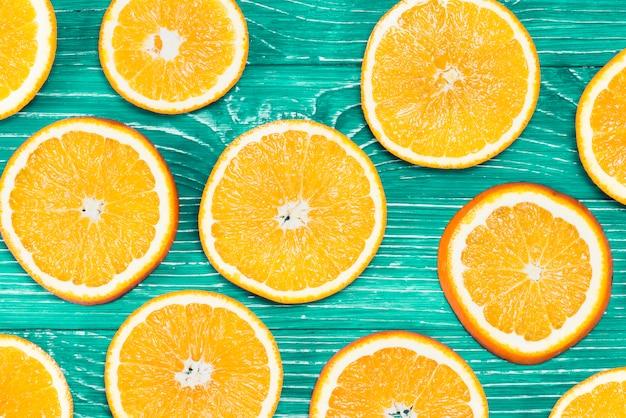 Composição de laranjas fatiadas em fundo verde