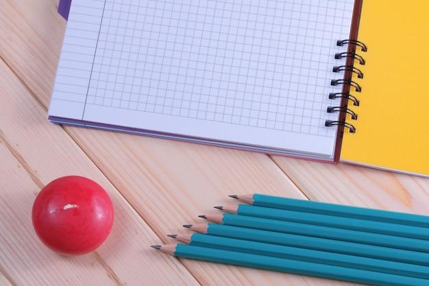 Composição de layout com caderno de folhas soltas em fundo de madeira com vela