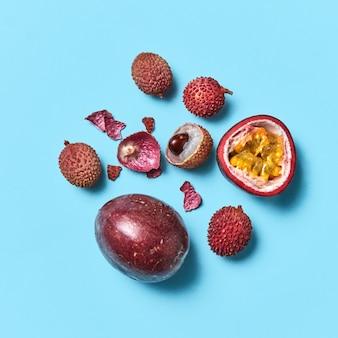 Composição de lichia de maracujá e casca de fruta sobre fundo azul com espaço de cópia. fruta tropical saudável. postura plana