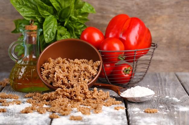 Composição de macarrão de trigo sarraceno colorido em uma tigela, tomates frescos na mesa de madeira
