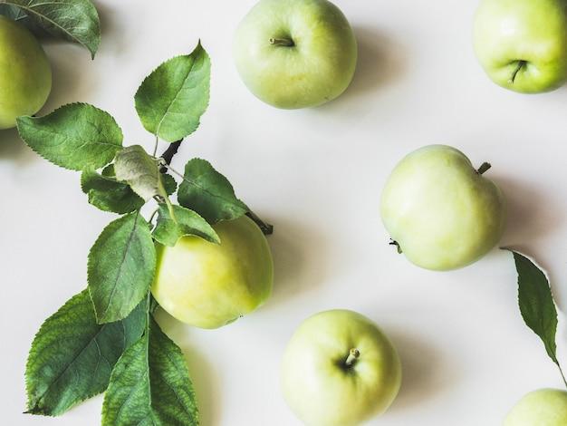 Composição de maçãs verdes e folhas em um fundo branco. papel de parede de frutas. vista superior, postura plana.