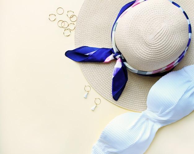 Composição de maiô de mulher, chapéu e acessórios de fachion em fundo biege