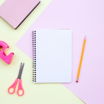 Composição de mesa knolling com caderno, lápis, tesoura e livro em rosa e amarelo de volta à escola