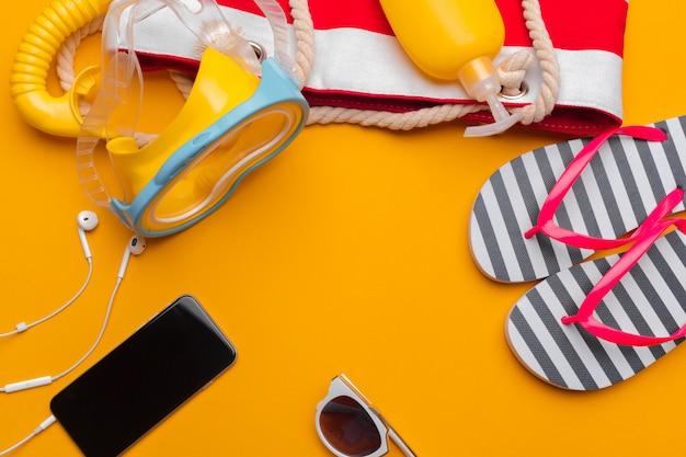 Composição de moda praia e acessórios em um fundo amarelo