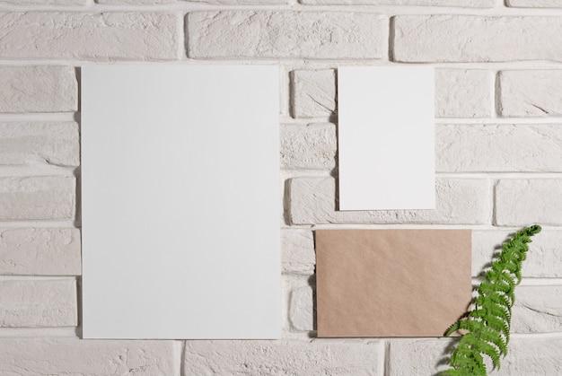 Composição de modelo de quadro de humor com cartões de papel em branco na parede de tijolos brancos com folha de samambaia
