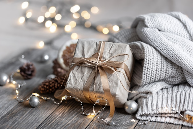 Composição de natal aconchegante com uma caixa de presente em um fundo desfocado em bokeh