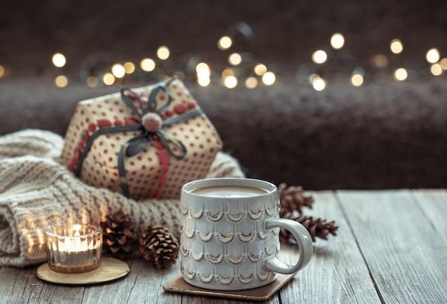 Composição de natal aconchegante com uma xícara e detalhes de decoração festiva em um fundo escuro borrado com bokeh.