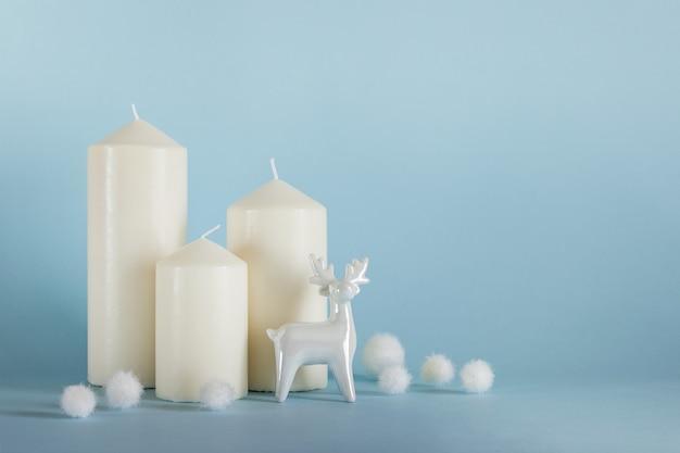 Composição de natal, ano novo com três velas brancas, renas de porcelana branca e bolas brancas sobre fundo amarelo azul. foto com espaço em branco de cópia.