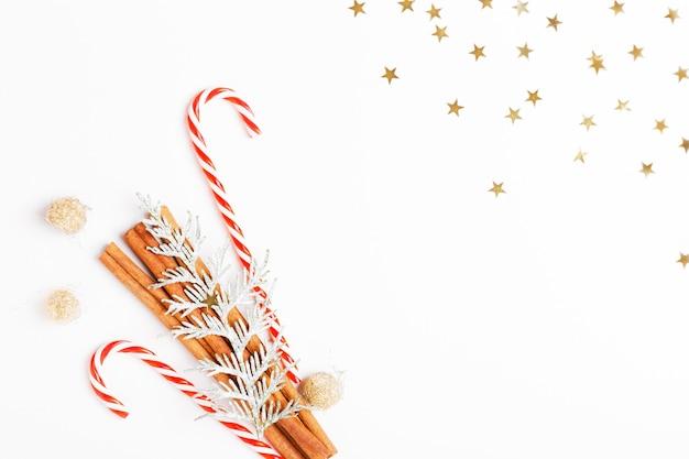 Composição de natal. árvore de natal feita de galhos de coníferas, bolas vermelhas, enfeites dourados sobre fundo branco.