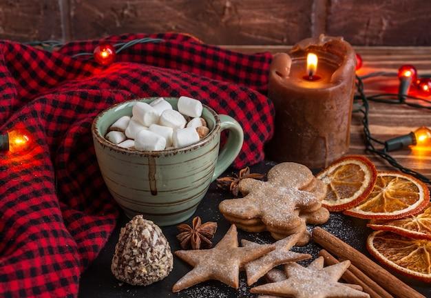 Composição de natal atmosférica uma xícara de cacau com velas de marshmallow, biscoitos de gengibre doces ...