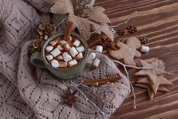 Composição de natal atmosférica: uma xícara de chocolate com marshmallows, biscoitos de gengibre, doces, canela